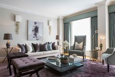 How to decorate with purple. Velvet nailhead upholster x-bench ottomans. Gold wall sconces. Living room decor ideas.