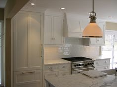 Traditional white kitchen with marble countertops and a white subway tile backsplash