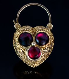 An Antique Heart Shaped Padlock Pendant Locket, Circa 1850. The gold puffed heart charm is finely engraved with scrolling foliage and embellished with three cabochon cut almandine garnets forming a trefoil. The back of the pendant is set with a glazed miniature compartment.