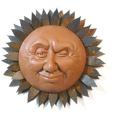 """Handcrafted Winking Sun Sculpture Handmade in North Carolina, the Winking Sun Sculpture instantly livens up any corner of your patio or garden with a face that cannot be resisted! Cut from 14-gauge steel with a rust finish, the double row of tight sun rays provide a harmonious frame for the sun face. The winking face is cast in dyed concrete and measures 8"""" in diameter. Overall, the sun sculpture measures 13"""" in diameter. Let this unique sculpture lighten up your indoor or outdoor space!"""