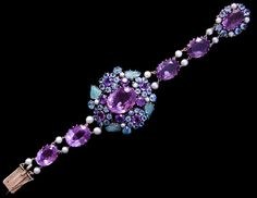 Dorrie Nossiter. An Arts and Crafts silver bracelet set amethysts, zircons, aquamarine clusters, carved emerald leaves and cultured pearls with gold bobbles and gold linking chain, c. 1930. Size: Length 18 cm. Central section 4.2 x 4.4 cm. Fitted case. Sold by Van Den Bosch. View 2.