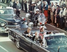 President and Mrs. John F. Kennedy smile at the crowds lining their motorcade route in Dallas, Texas, on November 22, 1963. Minutes later th...