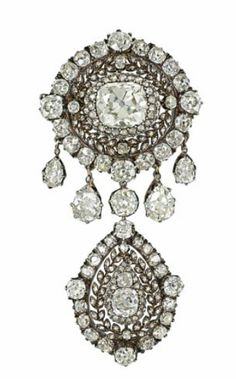 A LATE 19TH CENTURY DIAMOND BROOCH. Of target design, the principal cushion shaped old-cut diamond centre to a pierced rose-cut diamond laurel leaf surround and further cluster border, suspending a similarly designed cluster drop among a pear shaped diamond fringe to either side, mounted in silver and gold, circa 1880, 7.1cm long