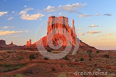 One of the iconic buttes of Monument Valley with red glow during sunset.