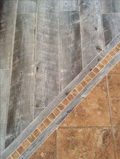 Lowe's porcelain tile in Natural Timber Ash (gray weathered barn board look) abutting our exisiting travertine. We were looking at pre-fab mosaic tiles for possible borders, but the contractor came up with a better idea, we love it!