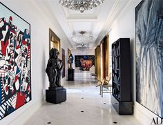 Merging three New York apartments into a single floor-through residence, the architecture firm Mojo Stumer Assoc. and interior designer James Aman created a dazzling showcase for art. The entrance gallery displays highlights from the homeowners' collection, including paintings by Jean Dubuffet (left), Jean-Michel Basquiat (far wall), and Jim Dine (right) | archdigest.com