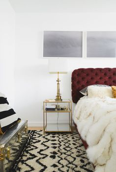 Noa Santos Manhattan Apartment: A gold lamp and bedside table pop against the white walls of a bedroom.