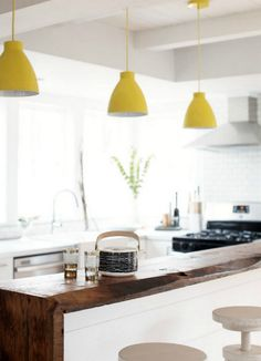 Love this wooden bar and the bright yellow lights against the cold white modern kitchen!