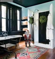 A Mexican wood-carved Santa Claus adds a holiday touch to the master bath as do a pair of small wreaths on the black shower doors, made to match the home's shutters.