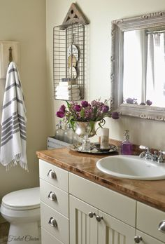 Faded  Charm: fresh flowers, clocks, silver containers, striped towels, salvaged finds in the bathroom