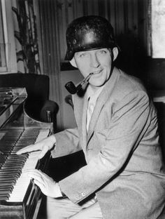 12th October 1944: American entertainer Bing Crosby playing the piano and wearing a German helmet. (Photo by Fox Photos/Getty Images)