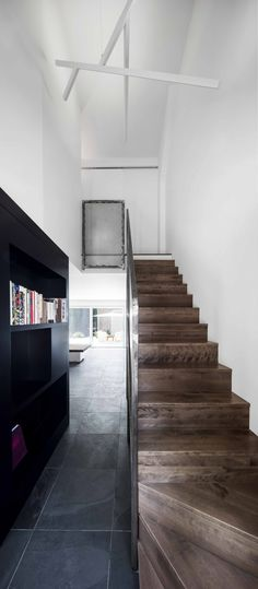 The staircase's steel guardrail and the custom black bookshelf create a link between the kitchen, the living space, and the entryway.