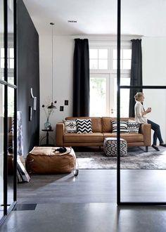 Cognackleurige leren bank, gecombineerd met zwart (wengé) en wit (bijv. lichte vloer)