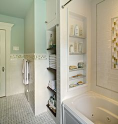 Custom shower/tub niche & floating reclaimed wood shelves in Family Bathroom Remodel by Tracey Stephens Interior Design