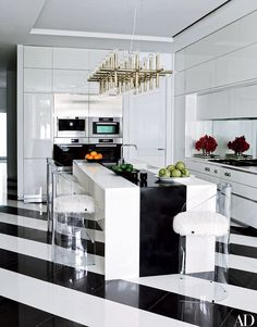 Willy Rizzo–style acrylic stools, cushioned in Mongolian lamb's wool, gather around the kitchen's Caesarstone island; the Robert Sonneman chandelier is 1970s, the cabinetry and hood are by Aran Cucine, the ovens and coffeemaker are by Miele, and the cooktop is by Gaggenau.