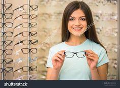 Young woman is choosing a glasses in optician store. Optician, Young Women, Stock Photos, T Shirts For Women, Glasses, Coat, Earrings, Fashion, Eyewear