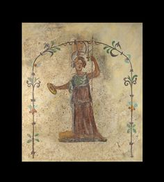 Fragment of Roman wall painting depicting Minerva wearing a red peplos and holding spear and phiale with a floral frame on white background. 2nd half 1st - 2nd century A.D..