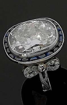 An Art Deco platinum, diamond and sapphire ring, circa 1920. Centring a large diamond weighing about 10 carats, framed by calibré sapphires and set with old-cut diamonds, mounted in platinum.