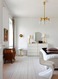 12 Ways to Use Panton Chairs: The white Panton chair is just one of a variety of styles in this bedroom, which includes a minimalist dresser and a bombé chest.