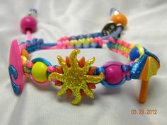 Made with 2mm bright multi-color satin cord, features surf board, sun & beach umbrella with pink, yellow, orange & blue wooden beads. There is a slip knot with two drawstrings that have pink & orange wooden end beads.    ITEM #: CAAB18    PRICE: $10
