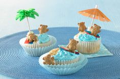 cool whip frosting dyed blue. Crumble gram crackers or brown sugar for beach. Mini marshmallow at base of cocktail umbrella. Flat colour candies for surf board. Teddy Grahams for bears.