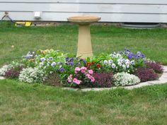 Flowers growing around septic tank cover. The bird bath sits on top of the cover. Septic Tank Covers, Flower Bed Designs, Outdoor Landscaping, Landscaping Ideas, Backyard Patio, Backyard Ideas, Outdoor Gardens, Bird Bath Garden, Outdoor Living