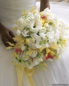 RP: UNIQUE BOUQUET - Tropical yellow-and-pink cattleya orchids punctuate ivory clouds of lisianthus and sweet peas. Lithe gloriosa lilies enliven the bouquet.