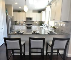 Love the gray and black stools, great combo with white cabinets, awesome grayish counter top, and awesome gray black splash