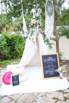 We could put one of our tepees up, decorated with flowers and twinkle lights, and put all the gifts in it ... Then a cozy chair for Lauren to sit in next to it. Would make Cute pictures for present opening time.
