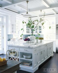 STEVEN GAMBREL  An upstate New York kitchen designed by Steven Gambrel features custom-made cabinets, marble countertops, and a new coffered ceiling; the light fixtures are vintage, and the refrigerator is by Viking.