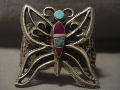 This is an exceptional vintage Navajo museum quality silver bracelet being one of the finest butterfly silver bracelets we have ever seen. The piece is solid sterling silver and check out the silver works, which are very complex swirling silver patterns with a huge butterfly in the center. The butterfly contains sugulite, natural blue and green turquoise stones. The large butterfly measures around 2-1/4 X 2-1/8. This bracelet is absolutely phenomenal. The width of the bracelet measures…
