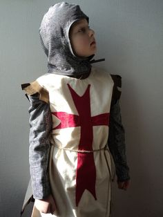 2-ply 100% cotton tabard with split sides and rope belt. Large red appliqued cross insignia. Leather dagging at hem and armlets. Hook and eye fastening at nape. PERFECT FOR ST GEORGE'S DAY!