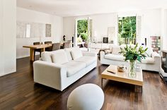 Achieve a serene, polished look with dark flooring and furniture in varying shades of white.  - GoodHousekeeping.com
