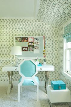 White and turquoise girl's bedroom features turquoise Moroccan tile wallpaper, Phillip Jeffries Moroccan Wallpaper in Blue, framing gray pin board over x-base desk with white lacquered top, Jonathan Adler Channing Desk, paired with turquoise octagon chair as well as turquoise blue jewelry box on modern white ottoman situated under window dressed in turquoise damask roman shade.