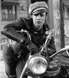 Simply iconic, Hollywood legend Marlon Brando solidified an iconic fashion moment as Johnny Strabler in the motorcycle gang drama The Wild One (1953). Posing on a bike, Brando wears a leather biker jacket and a biker cap stylishly tilted.