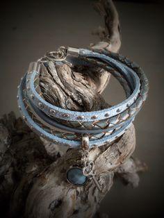 ijsblauwe wikkelarmband gemaakt van gevlochten leder, leder met studs en rond leder.