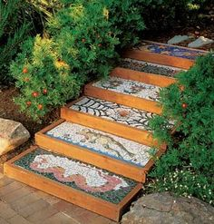 To add a whimsical touch to their garden path, the family covered plain concrete steps with mosaic art panels depicting a wiggling snake, a leaping frog, flowers, ladybugs, and other natural forms.  After the adhesive had dried thoroughly, they applied tile grout to fill