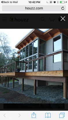 "Exterior: combination of blue hardy plank, cedar, black aluminum, large, ""store front"" windows, cable rails"