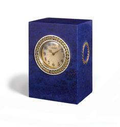 A RARE FABERGÉ CARVED LAPIS-LAZULI DESK CLOCK MOUNTED IN GOLD, SILVER, AND ENAMEL, WORKMASTER HENRIK WIGSTRÖM, ST. PETERSBURG, CIRCA 1910