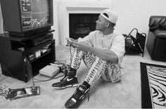 Will Smith playing Nintendo in a backwards hat, on a zebra rug, wearing Nike Air's, zubaz pants, and a Mariah Carey cd on the ground: