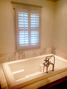 Plantation shutters over this beautiful tub give this bathroom the privacy needed.  Our Louverwood shutters are energy efficient and are perfect for humid rooms!