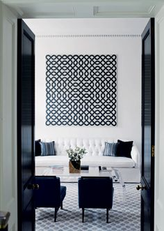 high gloss black #doors, graphic, overscaled #art positioned over a tailored and tufted white #sofa = design do
