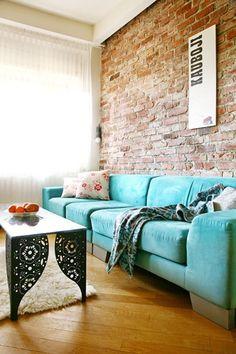 Parede com tijolos aparente em combinação com esse sofá turquesa, destaca o…