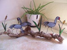 This stained glass scene of three Sand Hill Cranes are positioned on driftwood in various positions of feeding within the cattails.  The cranes are a wispy gray, with cattails of green and brown glass
