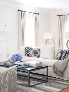 transitional white living room with white sofa, blue pillows and taupe drapes