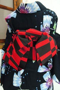 赤と黒で織り出された市松調の単の半幅帯です。