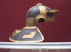 "The famous Niedermörmter Roman helmet of the 3rd century BCE. Side view. This style of helmet with hinged cheek pieces and a large neck protection was found in the river Rhine (now in the Mainz museum). It is a Weisenau type. Along with the elaborate applique and perforated brow, this helmet sports a unique design element on the crown: what are described as either ""Mice and cheese"" or ""Mice and bread"". Some experts call this model the most beautiful Roman helmet."