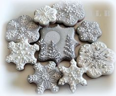 Snowflakes and an evening winter scene rendered in silver and white decorated cookies