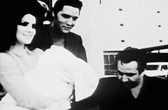 Elvis and Priscilla Presley, seen with Joe Esposito, exit the back door of Baptist Memorial Hospital in Memphis, TN, with five-day-old Lisa Marie. They are immediately greeted by press and a slew of cheering fans while ushered to a waiting Cadillac, February 5, 1968.