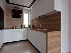 weiße grifflose Küchenfronten, Arbeitsplatte und Rückwand in Holzoptik